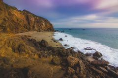 Secluded Pirate's Cove Beach at Sunset. With a colorful sky and ocean water flowing around rock formations, Point Dume, Malibu, California Royalty Free Stock Photos