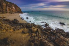 Secluded Pirate's Cove Beach at Sunset. With a colorful sky and ocean water flowing around rock formations, Point Dume, Malibu, California Royalty Free Stock Photography