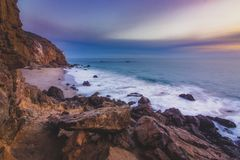Secluded Pirate's Cove Beach at Sunset. Secluded Pirate's Cove Beach at sunset with a colorful sky and ocean water flowing around rock formations, Point Stock Photography