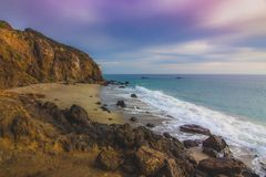 Secluded Pirate's Cove Beach at Sunset. Secluded Pirate's Cove Beach at sunset with a colorful sky and ocean water flowing around rock formations, Point Royalty Free Stock Photo