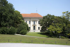 Secluded traditional white mansion with red rood in sunny day, h. Idden by green trees with blue and clear sky and a walk in the front in German Park stock images