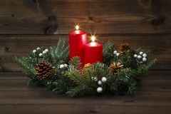 Second Advent - Decorated Advent wreath with two red burning candles on a wooden background Royalty Free Stock Photography