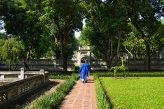 Second courtyard in Temper of Literature or Van Mieu with two men wearing old traditional long dress Ao Dai walking on courtyard.  Stock Photography