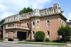 Second Empire Style Home. Vintage Second Empire style red brick house with mansard slate roof and stone baluster and Corinthian columns Stock Image