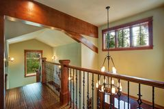 Second floor landing features stained handrails. And black iron spindles, beautiful chandelier hanging from the vaulted ceiling with wooden beams. Northwest Royalty Free Stock Images