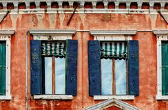 Second floor of old red house facade with wooden dark blue windows stock image