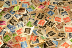 Second-hand British Postage Stamps Background. Pile of used British postage stamps used for mailing letters and parcels Stock Images
