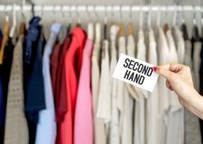 Second hand clothing. Shop. Woman holding a marketing sign Stock Image