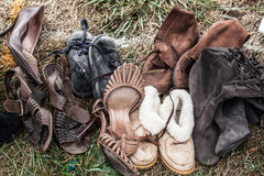 Second hand female shoes and boots on grass at garage sale. Mix of second hand leather women shoes and boots on sale at garage sale on grass for welfare royalty free stock photos