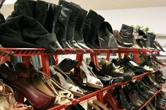 Second hand shoe rack. A shoe rack with second hand ladies shoes and boots stock image