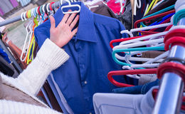 Second hand shop. Female hands choosing second hand clothes on a street market Royalty Free Stock Photography