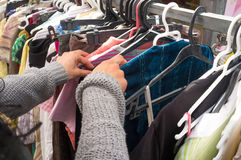 Second hand shop. Female hands rummaing in clothes  in a second hand shop Royalty Free Stock Images