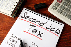 Second job tax. Second job tax written on a note Royalty Free Stock Photo