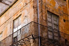 Second story of an old derelict building. Old dilapidated building with worn out windows and doors, crumbling plaster, wrought iron railing and peeling yellow Stock Image