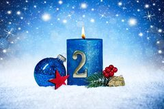 Second sunday of advent blue candle with golden metal number red decoration one on wooden planks in snow front of silver panorama stock images