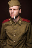 Second world war russian soldier smoking cigarette and looks at something Royalty Free Stock Image