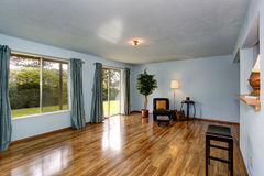 Secondary living room with blue interior and hardwood floor. Stock Image