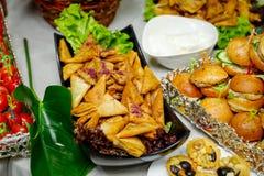 Secouez la table avec de mini hamburgers, apéritifs, légumes et casse-croûte photographie stock libre de droits