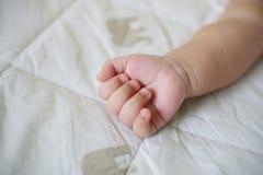 Secousse de bébé vers le haut de main sur le lit blanc Photos libres de droits