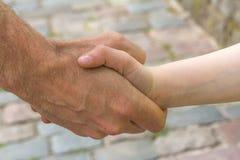 Secousse de main entre l'homme et le garçon Photo libre de droits
