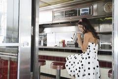 Secousse potable de jeune femme dans le wagon-restaurant images libres de droits
