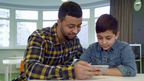 Secousses de garçon sur le smartphone du ` s de père banque de vidéos