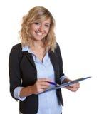 Secrétaire avec la note d'écriture de blazer bleu et de presse-papiers Photo stock