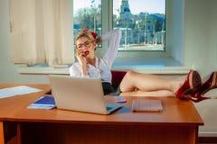 Secrétaire blond sexy parlant avec le téléphone au bureau avec des jambes Images stock