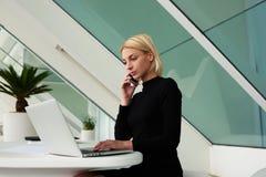 Secrétaire féminin appelant à son patron pour dire ce qu'elle a eu connaissance du nouveau projet dans le réseau sur l'ordinateur images libres de droits