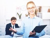 Secrétaire féminin d'heureuses affaires ayant le carton dans des mains photo libre de droits