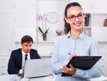Secrétaire féminin d'heureuses affaires ayant le carton dans des mains images libres de droits