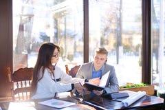 Secrétaire féminin parlant avec l'homme d'affaires au café et montrant le Ca Photo stock
