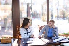 Secrétaire féminin parlant avec l'homme d'affaires au café et montrant le Ca Images stock