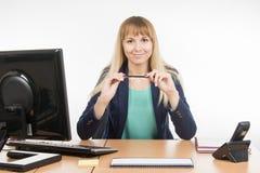 Secrétaire Girl s'assied à un stylo de table et de participation dans les mains Images stock