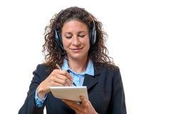 Secrétaire ou réceptionniste de sourire prenant des notes images libres de droits