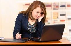 Secrétaire travaillant avec l'ordinateur portable et le comprimé photo libre de droits