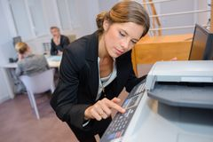 Secrétaire utilisant le photocopieur dans le bureau photo stock