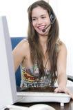 Secretária bonita no talkin do trabalho com auriculares Imagem de Stock Royalty Free