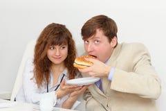 A secretária está alimentando sua saliência no local de trabalho Foto de Stock Royalty Free