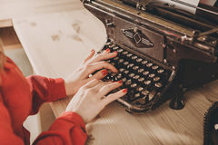Secretário na máquina de escrever velha com telefone Utilização da jovem mulher ty Fotografia de Stock