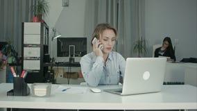 Secretário novo do escritório que trabalha no portátil e no telefonema de resposta video estoque