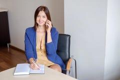 Secretário que fala no telefone celular e que escreve notas ao sentar-se em sua mesa Fotos de Stock Royalty Free