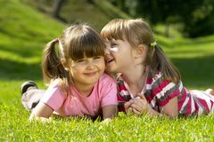 Secret. One little girl whispering a secret to another one. Lying on the grass in the park Royalty Free Stock Images