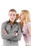 Secret. The girl silently tells something to the young man Royalty Free Stock Photography