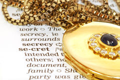 Secret. The word secret in English dictionary with a beautiful gold pendant lying next to it Royalty Free Stock Photo