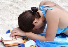 The Secret. The girl in deep thoughts about life secret while reading a book on Philipsburg town beach on St.Maarten island, Netherlands Antilles stock image