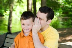 Secret. A father is sharing a secret with his son Stock Photos
