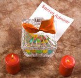 Secret Admirer Note. A note from a secret admirer is placed inside a candy dish beside two burning candles Stock Photo
