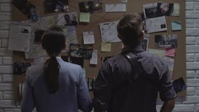 Secret agency teammates searching for criminal movements on investigation board stock footage