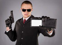 Secret agent. In a black suit with a red tie, gun and badge Stock Photos